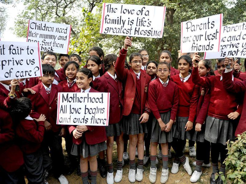 Schoolchildren hold up placards during a demonstration for the return of two children currently under the care of Norwegian social workers attended by other relatives and family friends outside the Norwegian embassy in New Delhi. (AFP photo/Sajjad Hussain)