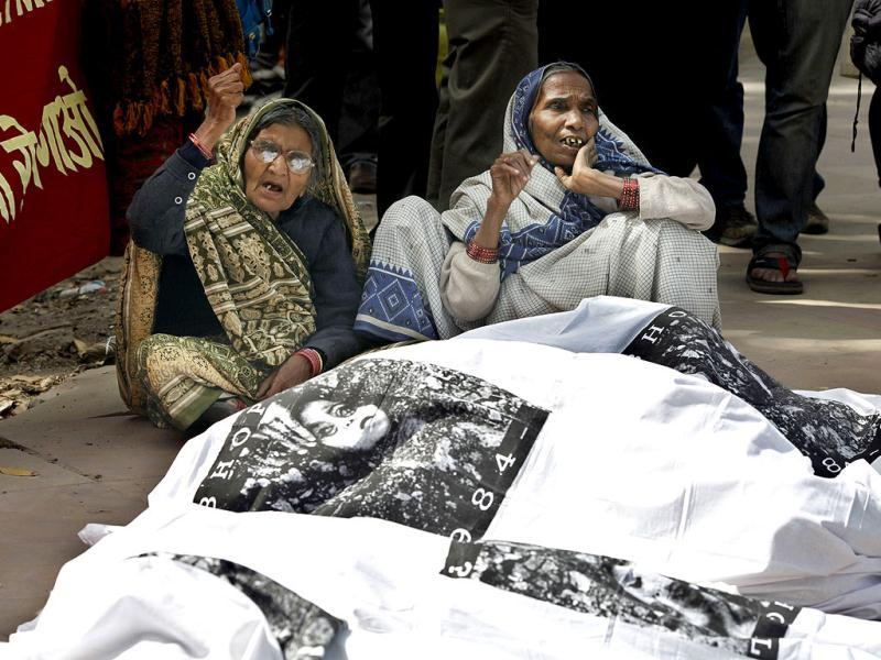 Victims of the 1984 Bhopal Gas tragedy shout slogans as others pose as dead bodies during a protest against Dow Chemicals sponsorship of the London 2012 Olympics, outside the sports ministry in New Delhi. AP/Saurabh Das