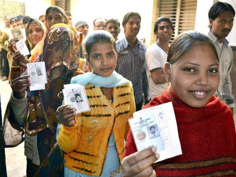Women voters show their identity cards as they wait in a queue to cast votes during sixth phase of Uttar Pradesh assembly elections in Mathura. PTI Photo