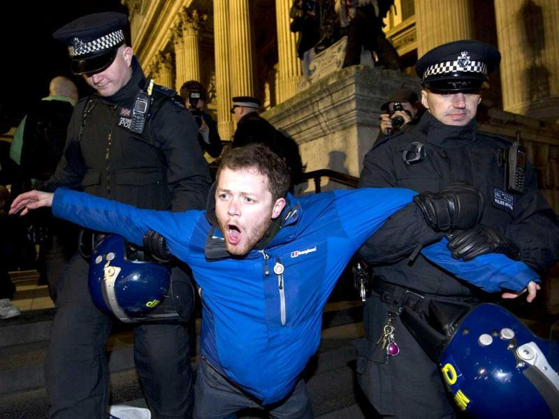 A protester is carried away by police at the Occupy protest camp outside Saint Paul's Cathedral in central London. (AFP photo/Carl Court)