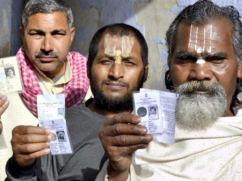 Sadhus show their voter identity cards as they wait in a queue to cast votes during sixth phase of Uttar Pradesh assembly elections in Mathura. PTI Photo
