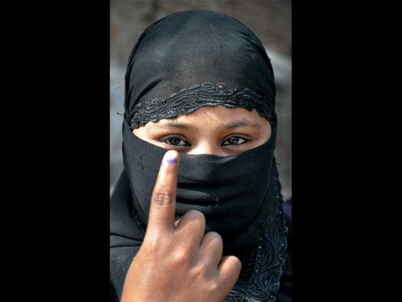 A burqa-clad voter shows her marked finger after casting vote during sixth phase of Uttar Pradesh assembly elections in Mathura. PTI Photo