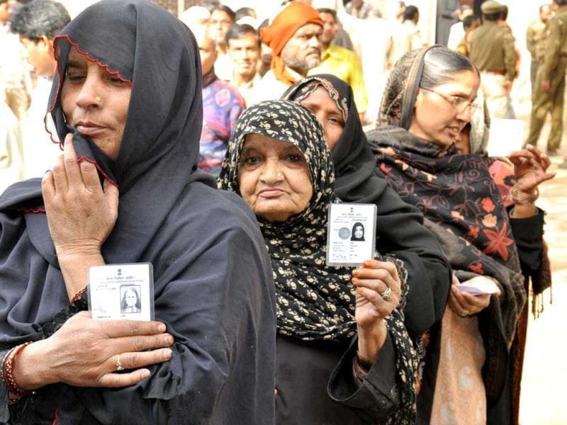 Women standing in a queue at a polling booth to cast their vote with their voter cards during the sixth phase of Uttar Pradesh assembly election in Mathura. Agencies