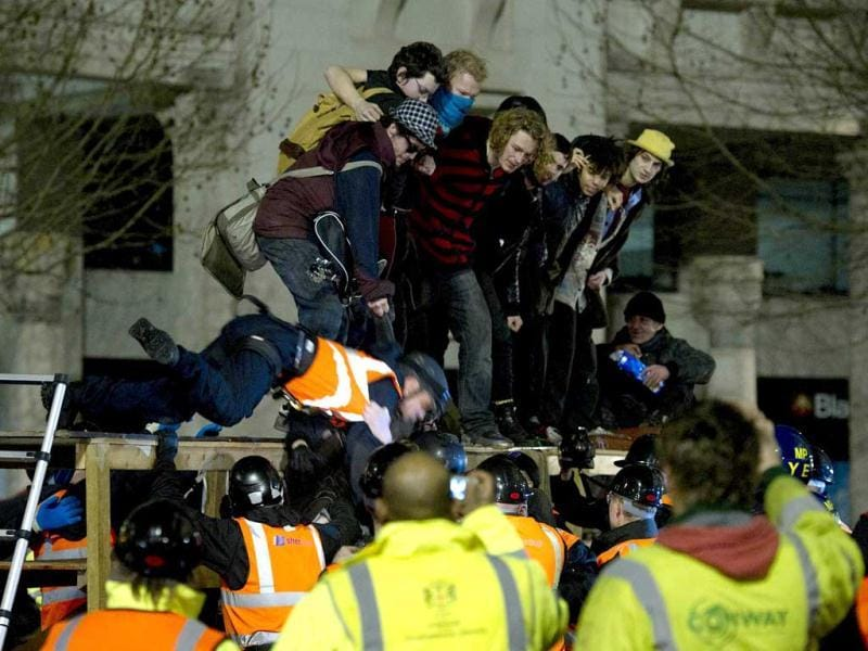 A bailiff is pulled from a makeshift barricade at the Occupy protest camp outside Saint Paul's Cathedral in central London as police and bailiffs evict demonstrators. (AFP photo/Carl Court