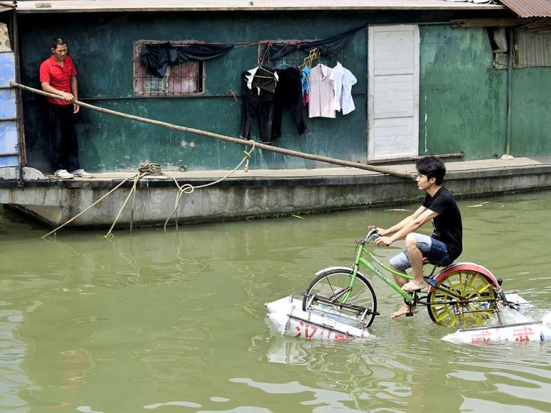 Lei Zhiqian rides a modified bicycle across the Hanjiang River, a tributary of the Yangtze River in Wuhan, Hubei province. The bicycle, equipped with eight empty water containers at the bottom, was modified by Lei's instructor Li Weiguo, who hopes to put his invention into the market. Reuters/China Daily