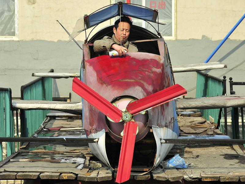 Li Jingchun, a 58-year-old farmer, sprays paints onto his self-made aircraft on top of his house in Xiahe village located in Shenyang, Liaoning province. The 5m long, 1.5m wide plane, mostly made of recycled iron plates, cost the aircraft enthusiast and his family two years and more than 40,000 yuan ($6,349), according to local media. Reuters/Sheng Li