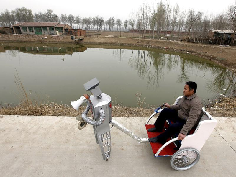 Farmer Wu Yulu, 48, rides in a cart pulled by his walking robot near his home in a village at the outskirts of Beijing. Hobby inventor Wu, who started to build robots in 1986, has invented 47 robots with different functions like jump, paint, drink, pull cart, massage, and help cooking. He will display more than 30 his robots during Shanghai World Expo 2010, and he wants to promote his practical robots into market by the Expo. Reuters/Petar Kujundzic