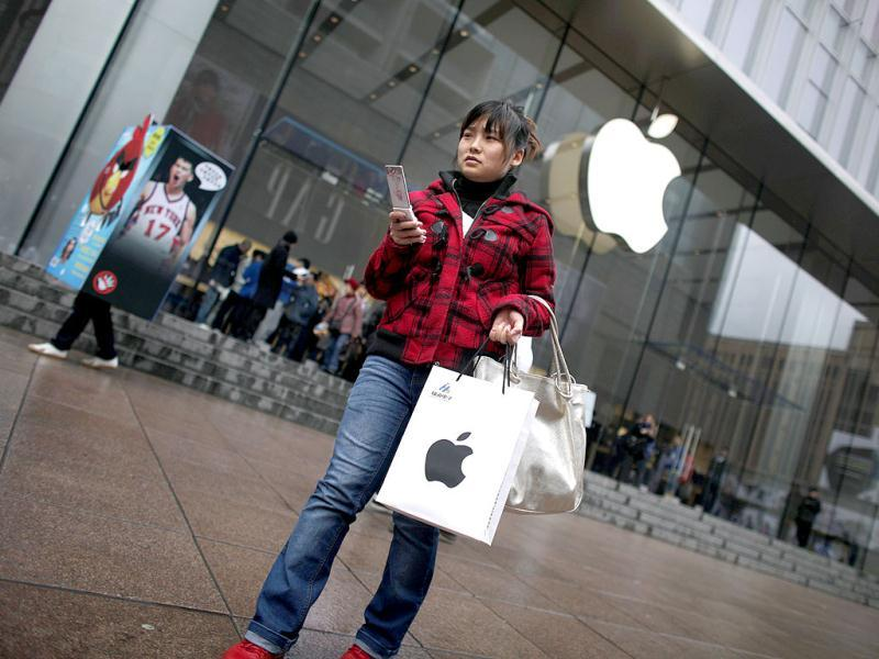 A customer walks out after shopping at an Apple store in downtown Shanghai. Reuters/Carlos Barria