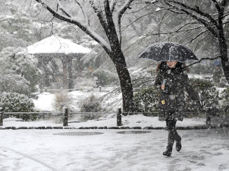 People walk under snow on the streets in the downtown Tokyo. AFP Photo/Toru Yamanaka