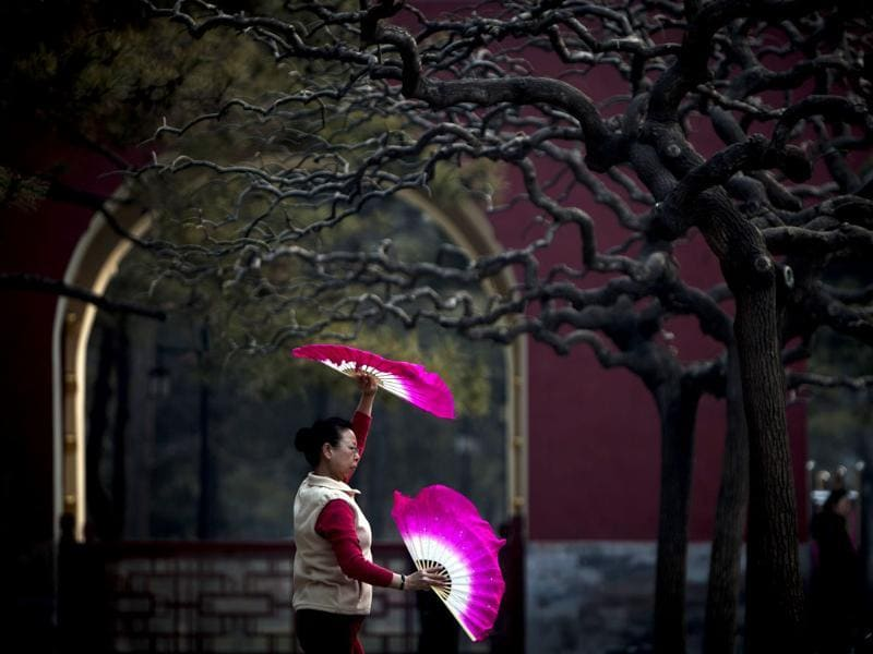 A Chinese woman performs morning exercise with fans at the Ditan park in Beijing, China. AP Photo/Andy Wong