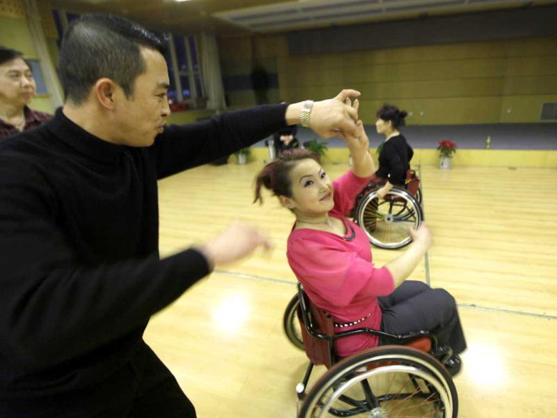 An instructor helps physically disabled Dong Jingli to practise modern dance at a disabled persons activity center in Beijing. Two times a week, a group of 42 dancers including 24 women with physical disabilities, mostly between the ages of 21 and 62, from the commonwealth organization of the Beijing Disabled Dance Team practice modern dance using wheelchairs since 2009, according to the organizer. Reuters/Jason Lee.