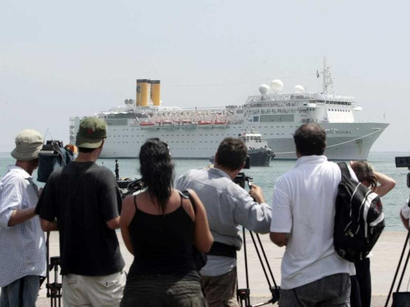Members of the media and onlookers watch the Costa Allegra cruise ship as it is towed in Victoria harbor, Seychelles Island. The disabled cruise ship arrived in port in the island nation of the Seychelles on Thursday morning after three days at sea without power. AP Photo/Gregorio Borgia