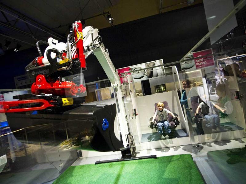 Kids play with an Excavator as it is displayed at the