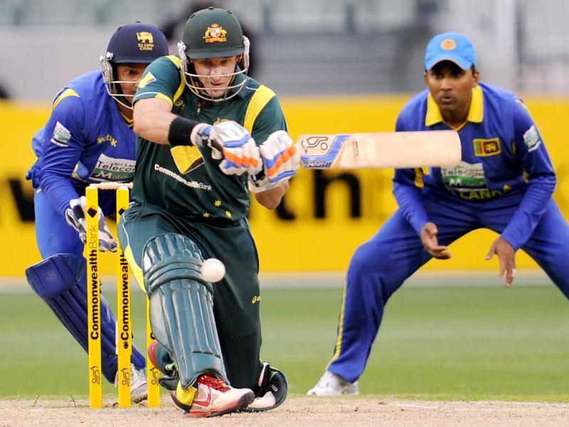 Australian batsman Michael Hussey (C) sweeps a delivery as Sri Lankan wicketkeeper Kumar Sangakkara (L) and fieldsman Mahela Jayawardene (R) look on in their one-day international cricket match at the Melbourne Cricket Ground (MCG). AFP Photo/William West
