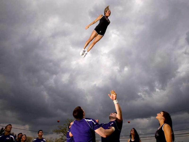 This photo won second place (picture story/sports) in the White House News Photographers Association (WHNPA) 2012 contest. Baltimore Ravens cheerleader Jaime flies in the air during stunt practice at cheerleader training camp at Deep Creek, Maryland, May 20, 2011. Reuters/Jason Reed