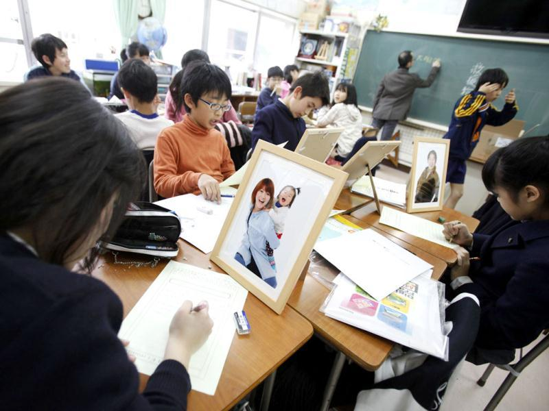 Sixth grade students from Keimei Gakuen elementary school in Akishima, on the outskirts of Tokyo, write letters and frame portraits of earthquake survivors as part of the 3.11 Portrait Project. Reuters/Yuriko Nakao