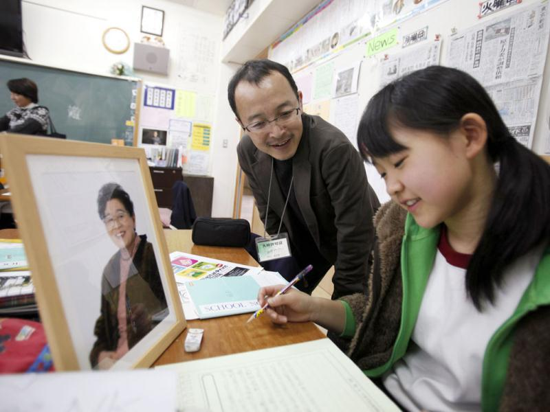 Japanese photographer Nobuyuki Kobayashi talks to a sixth grade student from Keimei Gakuen elementary school in Akishima, on the outskirts of Tokyo, as she writes a letter to an earthquake survivor as part of the 3.11 Portrait Project. Reuters/Yuriko Nakao