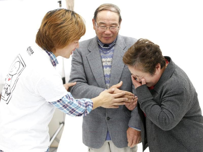 Photographer Kenichi Funada encourages an elderly couple to hold hands before having their portrait taken as part of the 3.11 Portrait Project at the Midorigaoka temporary shelter in Koriyama, Fukushima. Reuters/Yuriko Nakao