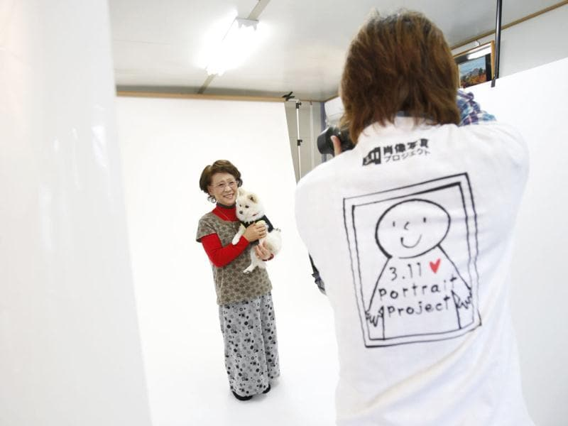 Photographer Kenichi Funada takes a portrait of Katsuko Abe with her pet dog Kaede as part of the 3.11 Portrait Project at the Midorigaoka temporary shelter in Koriyama, Fukushima. Reuters/Yuriko Nakao