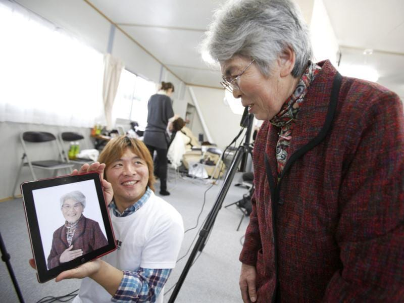 Photographer Kenichi Funada shows Tsugiko Miyajima her portrait on his iPad after taking part in the 3.11 Portrait Project at the Midorigaoka temporary shelter in Koriyama, Fukushima. Reuters/Yuriko Nakao