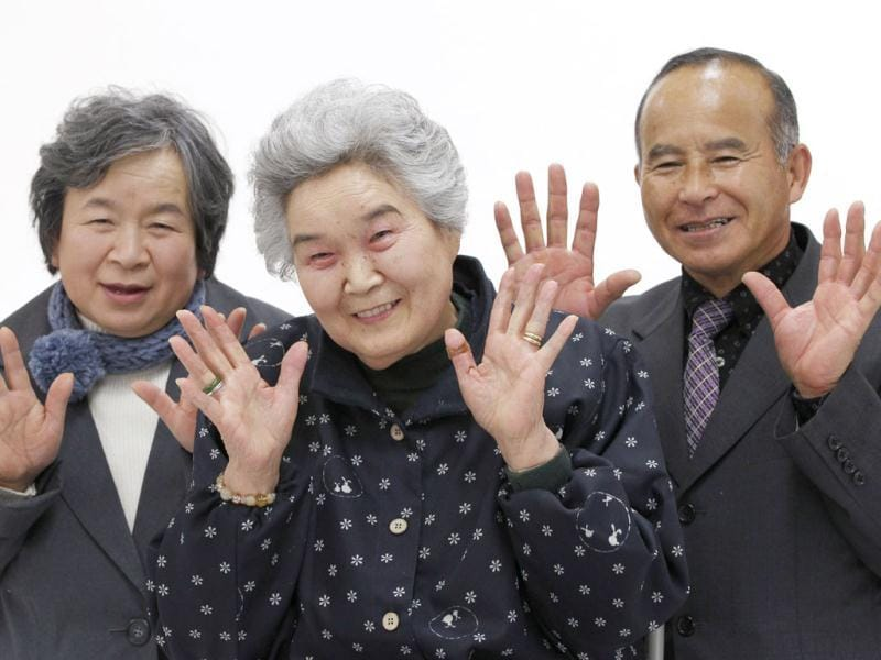 Misako Yokota, flanked by her daughter and son in law, pose for a portrait as part of the 3.11 Portrait Project at the Midorigaoka temporary shelter in Koriyama, Fukushima.  Reuters/Yuriko Nakao