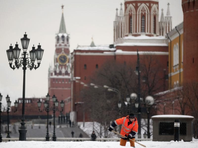 A worker shovels snow, with the Kremlin seen in the background, in central Moscow. Reuters/Pawel Kopczynski