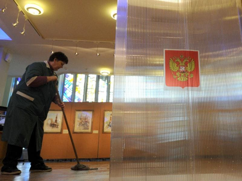 A cleaner scrubs the floor next a ballot box at a polling station in Moscow, while preparing for the upcoming voting. AFP Photo/Kirill Kudryavtsev