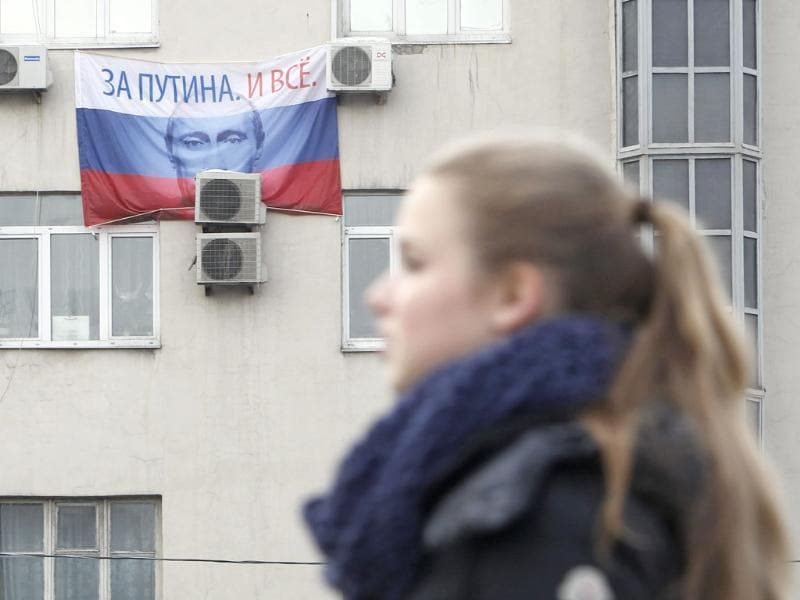 A flag for presidential campaign poster for Russia's Prime Minister Vladimir Putin hangs out of windows of a dwelling house in Moscow. The flag reads: For Putin. And that's all. Reuters/Denis Sinyakov
