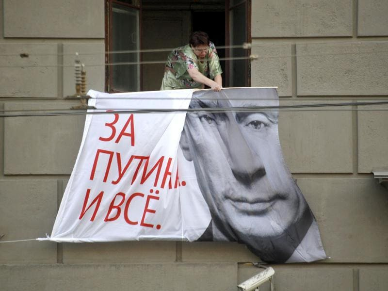 A Russian woman tries to remove an election poster from the wall of an apartment house in downtown Moscow. Friday is the last day, before Sunday's presidential elections, when election campaign posters are allowed. The poster reads: For Putin, Just It. (AP Photo/Mikhail Metzel)