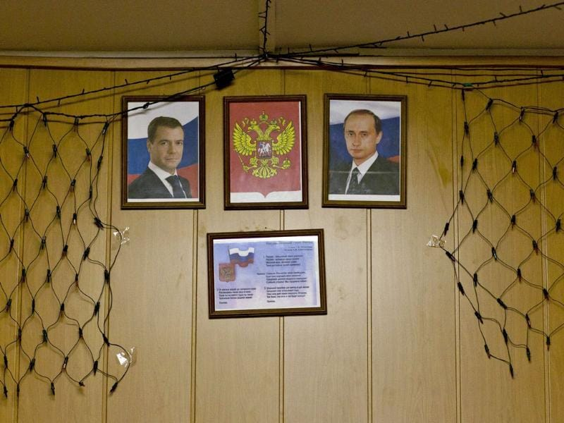 Portraits of Russian President Dmitry Medvedev (L) and Prime Minister Vladimir Putin are displayed at the foyer of a polling station in the settlement of Pogoreloe Gorodishche, some 170 km west of Moscow. Reuters/Thomas Peter
