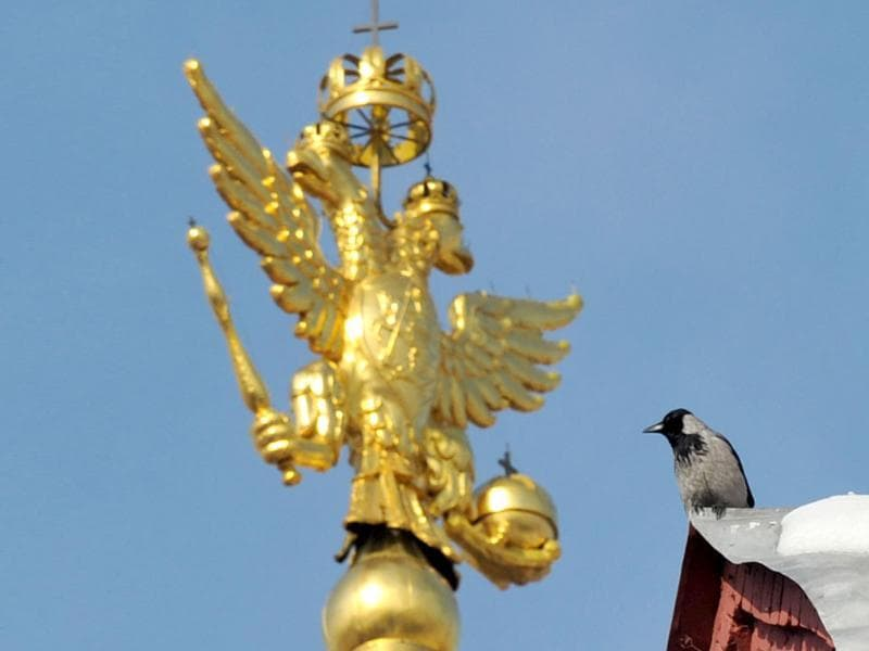 A crow sits next to Russian national emblem, double headed eagle, on top of Historical Museum at the Red Square in Moscow. AFP Photo/Sergei Supinsky
