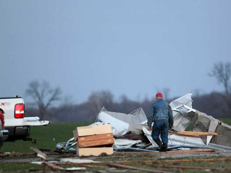 A resident works to clear storm damage after three tornadoes moved through the area in Chelsea, Indiana. A series of tornadoes tore through the U.S. midsection on Friday, killing at least four people in the hard-hit state of Indiana, and blowing apart homes and flattening buildings across the region. REUTERS/ UNI PHOTO-6R