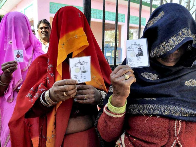 Women voters show their identity cards as they wait to cast their votes at a polling station, during the final phase of Uttar Pradesh assembly elections in Moradabad district. PTI Photo.