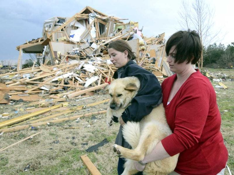 Lisa Copeland, right, and Kacie Rose carry a dog to a safe place before a second round of storms approaches in Ooltewah, Tennesse. Powerful storms stretching from the Gulf Coast to the Great Lakes flattened buildings in several states, wrecked two Indiana towns and bred anxiety across a wide swath of the country in the second powerful tornado outbreak this week. (AP Photo/Chattanooga Times Free Press, Angela Lewis)