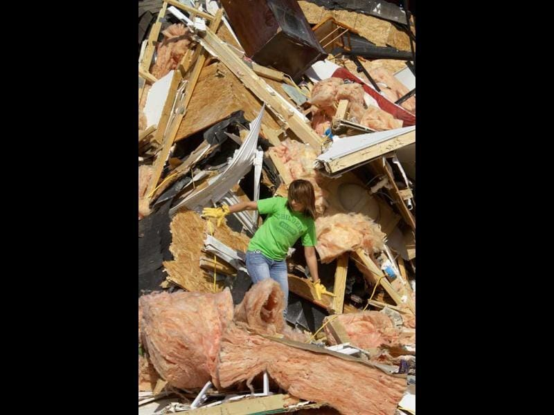 Brooke Hill helps a friend salvage and clean up what they can from her home in Harrisburg, Ill. A pre-dawn twister flattened entire blocks of homes Wednesday as violent storms ravaged the Midwest and South. (AP Photo/Seth Perlman)