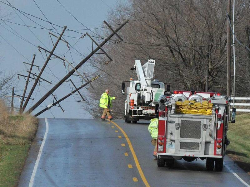 A utility worker inspects downed utility poles that forced the closure of Indiana 61 north of Boonville, Indiana. Severe storms knocked out power in many areas around the town. (AP Photo)
