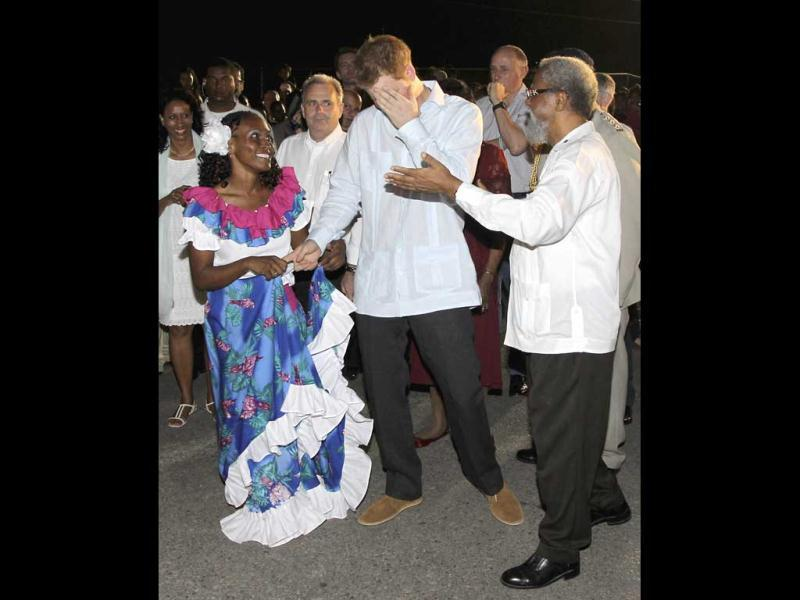 Belize's governor general Sir Colville Young (R) gestures for Britain's Prince Harry (C) to take part in a dance at a Jubilee Block Party in Belmopan, Belize. Reuters/Chris Jackson/Pool