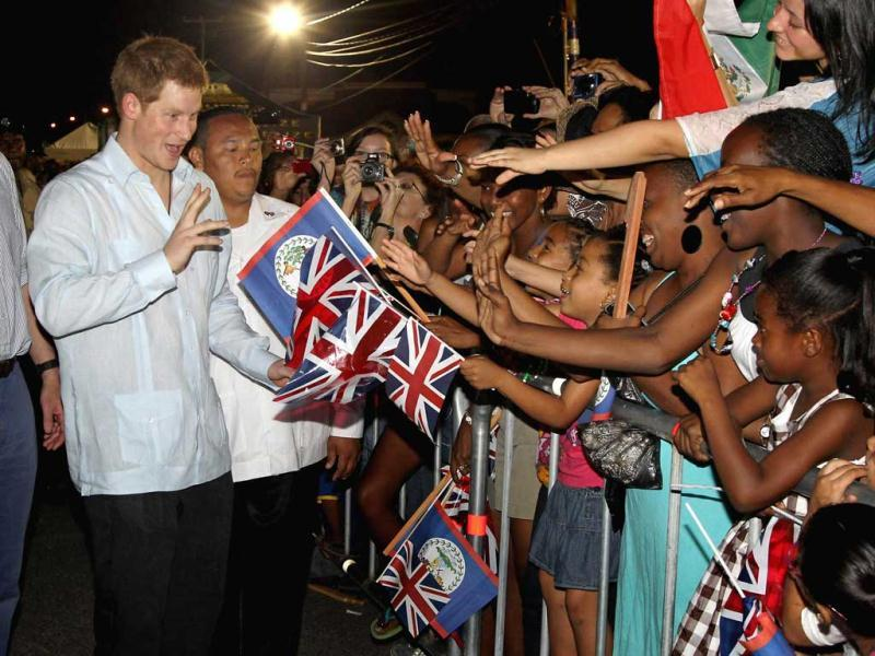 Britain's Prince Harry, left, meets locals during a walkabout at a block party in the newly-named Queen Elizabeth II Boulevard, capital Belmopan, Belize, central America. AP Photo/PA, Chris Jackson