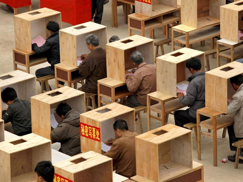 Villagers write ballots at voting booths during an election to select village committees at a polling station set up outside a school in Wukan village, China's southern Guangdong province. AP Photo/Vincent Yu