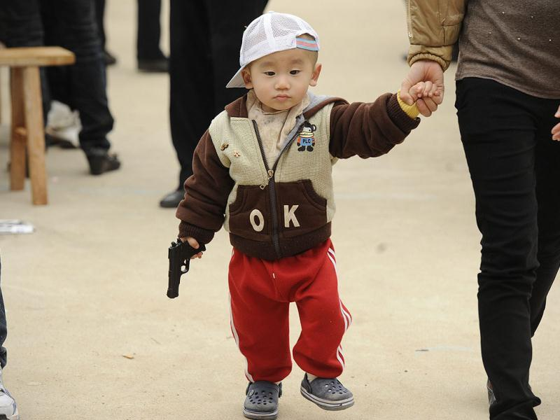 A childs walks with his toy gun after his mother cast her vote in village elections in Wukan, China's southern Guangdong province. Residents of the small village went to the polls in a leadership election being hailed as a milestone for those demanding more say in the running of the one-party state. AFP Photo/Peter Parks