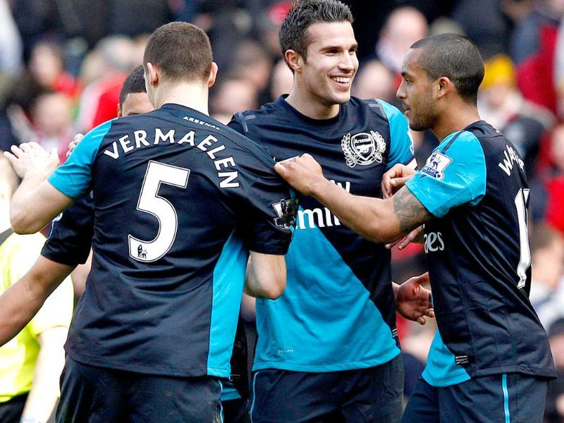 Arsenal's Robin van Persie celebrates with team mates following their English Premier League soccer match against Liverpool at Anfield in Liverpool, northern England. (Reuters)