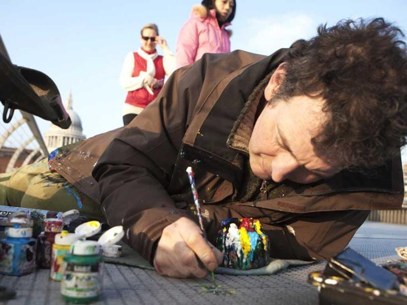Artist Ben Wilson paints on a piece of discarded chewing gum on the Millennium Bridge, in London. Reuters/Finbarr O'Reilly