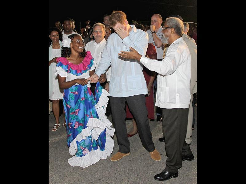 Governor General of Belize Sir Coleville Young, right, gestures for Britain's Prince Harry to dance with the woman holding his finger , as he meets local people during a walkabout at a