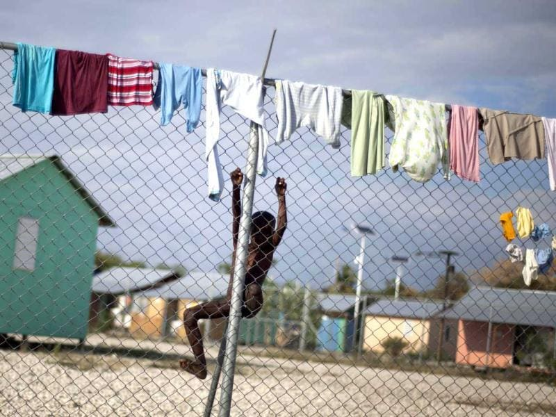 A child whose leg whose right leg was amputated due to an injury suffered in the 2010 earthquake, climbs a fence to get to his clothes hanging out to dry at La Piste camp in Port-au-Prince, Haiti. AP Photo/Ramon Espinosa