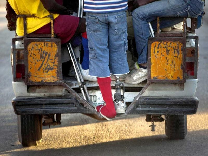 A resident of La Piste camp, Jean Lacroix, 27, whose right leg was amputated due to an injury suffered in a motorcycle accident, rides a public taxi to soccer practice in Port-au-Prince, Haiti. AP Photo/Ramon Espinosa