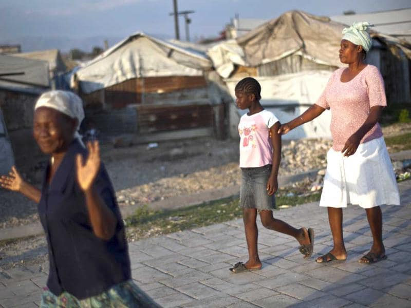 Visually impaired Nazilia Dicque, 44, right, is led out of La Piste camp by her daughter Julienne to a nearby church in Port-au-Prince, Haiti. AP Photo/Ramon Espinosa