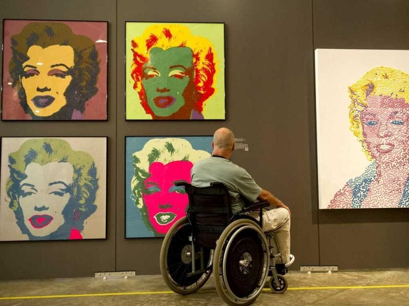 A visitor enjoys paintings from Andy Warhol's series