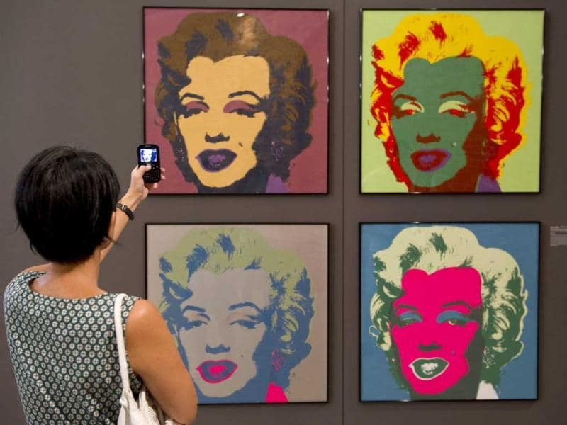 A visitor takes a picture of paintings from Andy Warhol's series