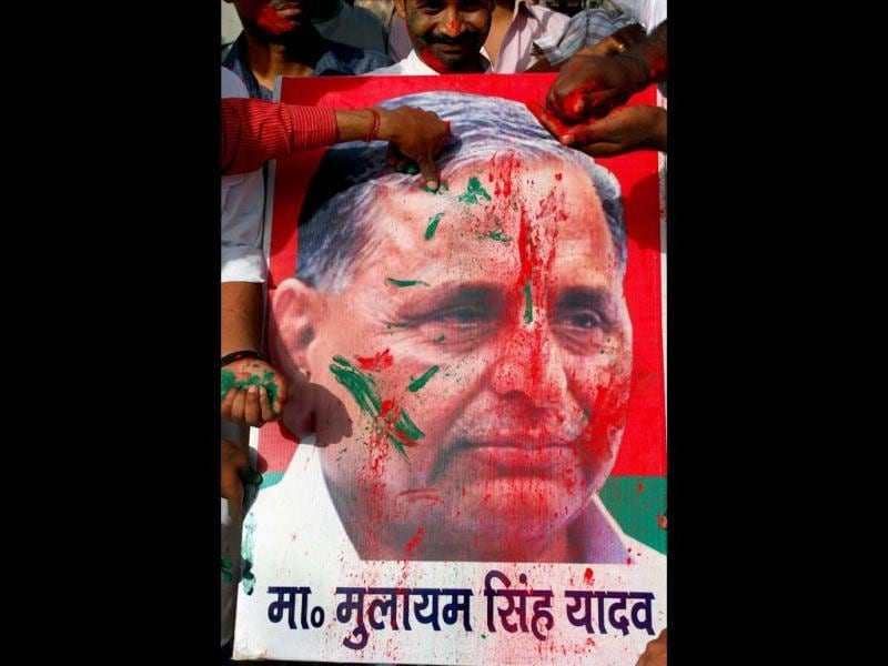 Samajwadi Party workers apply colour to a poster of party chief Mulayam Singh Yadav in Allahabad as they celebrate the success of their party. PTI