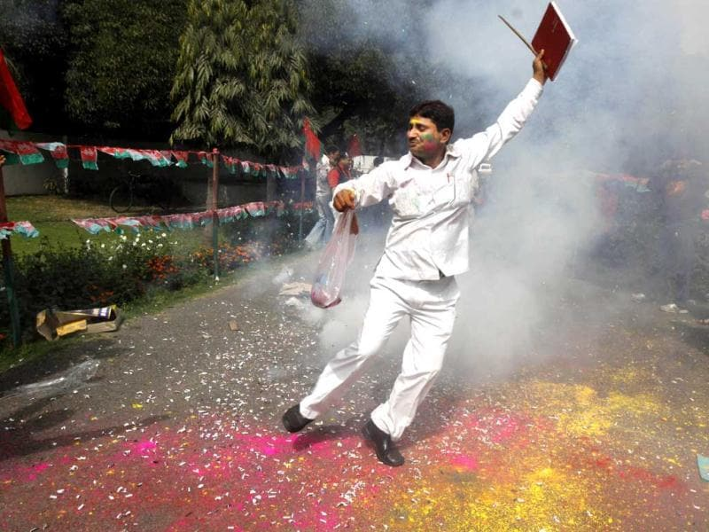 A Samajwadi Party supporter dances amid smoke of bursting crackers as he celebrates the success of party leader Mulayam Singh Yadav outside the party office in New Delhi. AP/Pankaj Nangia
